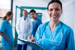 Portrait of smiling surgeon writing on clipboard. In hospital Royalty Free Stock Image