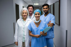 Portrait of smiling surgeons and doctor standing in corridor Royalty Free Stock Photo