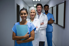 Portrait of smiling surgeons and doctor standing in corridor Stock Photos