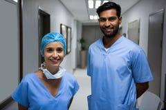 Portrait of smiling surgeons standing in corridor Stock Photo
