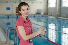 Portrait of smiling swim coach holding clipboard at poolside.  royalty free stock images