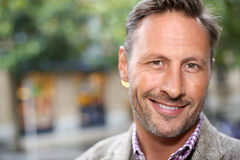 Portrait of smiling tanned man in street royalty free stock image