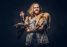 Portrait of a tattoed redhead hipster male with long luxuriant hair and full beard dressed in a t-shirt and jacket holds. Portrait of a smiling tattoed redhead stock photography