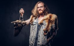Portrait of a tattoed redhead hipster male with long luxuriant hair and full beard dressed in a t-shirt and jacket holds. Portrait of a smiling tattoed redhead royalty free stock photos
