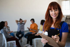 Portrait of smiling teacher holding clipboard with students talking in background Stock Photography
