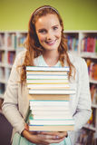 Portrait of smiling teacher holding a stack of books in library Stock Photography