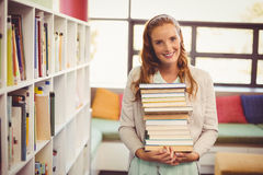 Portrait of smiling teacher holding a stack of books in library Stock Image