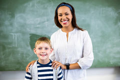 Portrait of smiling teacher and schoolboy standing in classroom Royalty Free Stock Image