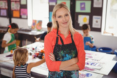 Portrait of smiling teacher standing with arms crossed. In drawing class royalty free stock photography
