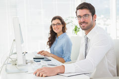 Portrait of smiling team with glasses at desk Stock Photography