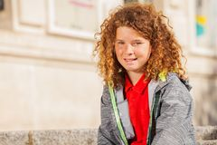 Teenage curly-haired boy looking at camera. Portrait of smiling teenage curly-haired boy sitting outdoors and looking at camera Stock Image