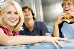 Portrait of a smiling teenage girl with her friends in a diner Stock Image