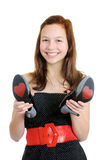 Portrait of a smiling teenage girl holding high heel shoes isolated Stock Photos
