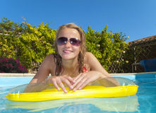 Portrait of smiling teenage girl laying on pool raft in swimming pool Royalty Free Stock Photo