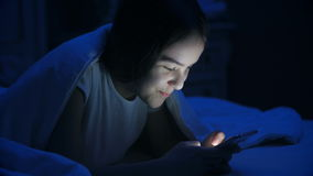 Portrait of smiling teenage girl lying under blanket and typing message on mobile phone stock video
