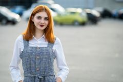 Portrait of a smiling teenage girl with red hair and clear eyes wearing fashionable casual dress standing outside in warm summer