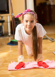 Portrait of smiling teenage girl washing floor with cloth Stock Image