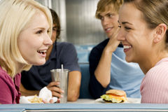 Portrait of smiling teenage girls with her friends in a diner Stock Photo