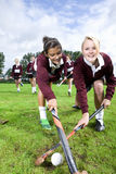Portrait of smiling teenage girls playing field hockey Stock Photography