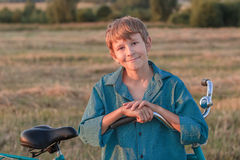 Portrait of smiling teenager boy with bike. Portrait of smiling teenager boy with a bike at sunset Stock Images