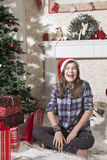 Portrait of smiling teenager girl in santa hat near christmas Stock Photography