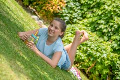 Portrait of smiling teenager lying in the grass Stock Photo