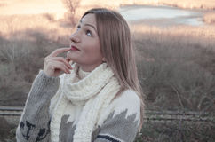 Portrait of a smiling thinking woman looking up. Beautiful smiling girl in cardigan  and white scarf, in the field Royalty Free Stock Photo