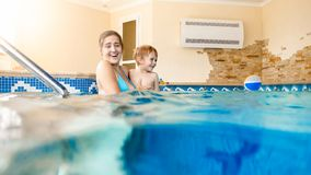 Portrait of happy smiling toddler boy learning swimming with mother in pool. Family having fun and relaxing in swimming. Portrait of smiling toddler boy learning stock photo