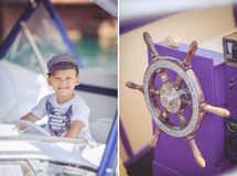 Portrait of smiling toddler boy sitting in the boat on the river. Cute little sailor boy having fan near boats on pier near the sea. Outdoor Royalty Free Stock Photo