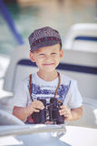 Portrait of smiling toddler boy sitting in the boat on the river. Cute little sailor boy having fan near boats on pier near the sea. Outdoor Royalty Free Stock Photos