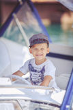Portrait of smiling toddler boy sitting in the boat on the river. Cute little sailor boy having fan near boats on pier near the sea. Outdoor Stock Photography