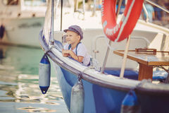 Portrait of smiling toddler boy sitting in the boat on the river Royalty Free Stock Image
