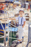 Portrait of smiling toddler boy sitting in the boat on the river. Cute little sailor boy having fan near boats on pier near the sea. Outdoor Royalty Free Stock Images