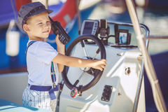 Portrait of smiling toddler boy sitting in the boat on the river. Cute little sailor boy having fan near boats on pier near the sea. Outdoor Royalty Free Stock Image