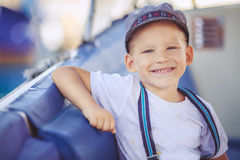 Portrait of smiling toddler boy sitting in the boat on the river. Cute little sailor boy having fan near boats on pier near the sea. Outdoor Royalty Free Stock Photography