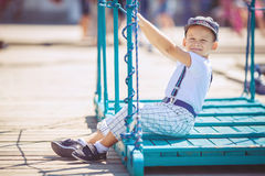 Portrait of smiling toddler boy sitting in the boat on the river. Cute little sailor boy having fan near boats on pier near the sea. Outdoor Stock Photo