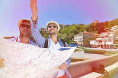 Portrait of a smiling tourist with map and bag.  Royalty Free Stock Photo