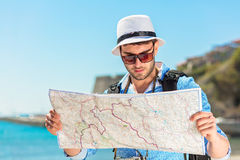 Portrait of a smiling tourist with map and bag.  Royalty Free Stock Images