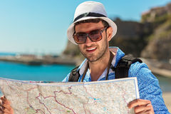 Portrait of a smiling tourist with map and bag.  Stock Photos
