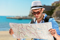 Portrait of a smiling tourist with map and bag.  Royalty Free Stock Photography