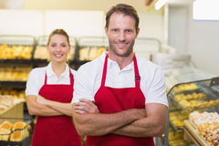 Portrait of smiling two bakers with arms crossed. In bakery Royalty Free Stock Photos