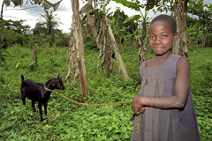 Portrait of smiling Ugandan goatherd with goat. Uganda, Luweero district, village Kalasa: A girl walking her goat in the countryside. She loves the animal and is stock image