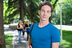Portrait of Smiling University Male. Portrait of young male smiling while his classmates walking in the background Stock Image
