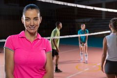 Portrait of smiling volleyball player by teammates. Portrait of smiling female volleyball player by teammates at court Royalty Free Stock Images