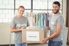 Portrait of smiling volunteer holding clothes donation box Stock Image