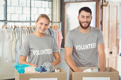 Portrait of smiling volunteers separating donations clothes Stock Photography