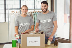 Portrait of smiling volunteers separating donations stuffs Stock Photos