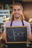 Portrait of smiling waiter holding chalkboard with open sign Royalty Free Stock Photo