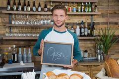 Portrait of smiling waiter holding chalkboard with open sign Stock Photos