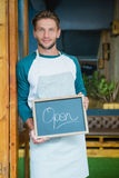 Portrait of smiling waiter holding chalkboard with open sign Stock Photography